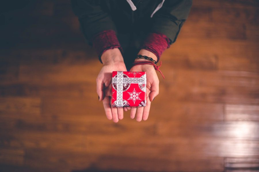 Person giving a small wrapped gift