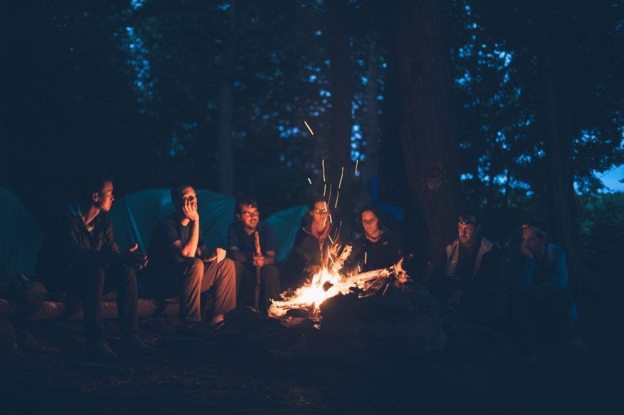 Group of friends warming up around a bonfire in woods